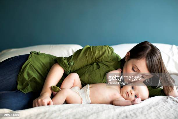 mother kissing daughter while lying on bed - diaper girl photos et images de collection