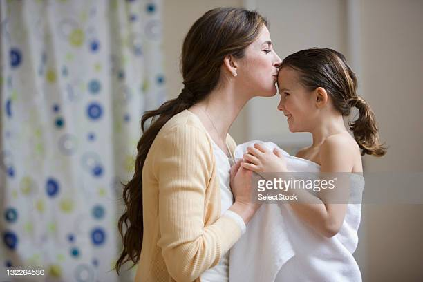 mother kissing daughter's forehead after bath - forehead stock pictures, royalty-free photos & images