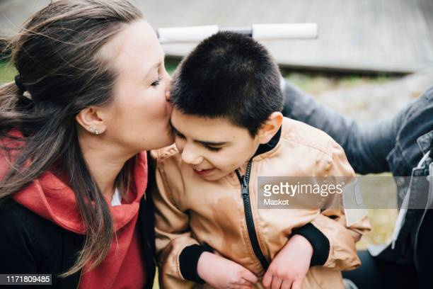 mother kissing disabled son sitting on wheelchair in yard - minder validen stockfoto's en -beelden