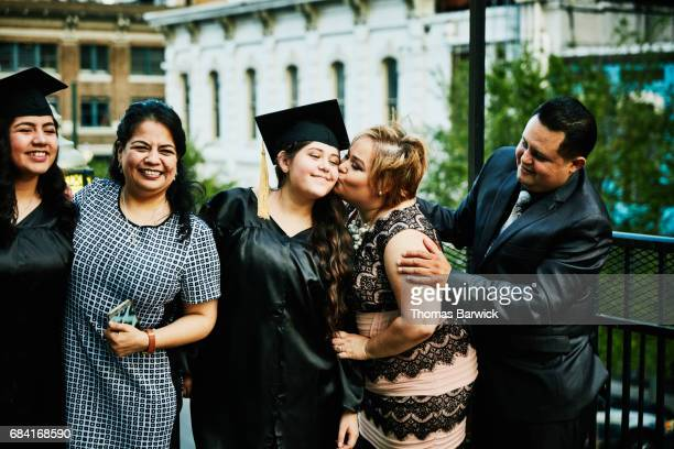 Mother kissing graduating daughter during family celebration on restaurant deck