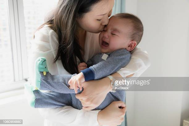 mother kissing her baby - moms crying in bed stock photos and pictures