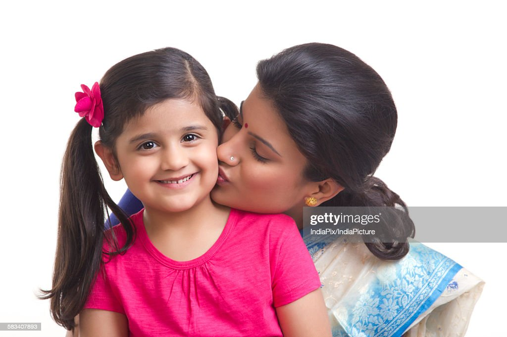 Mother kissing her daughter on the cheek : Stock Photo