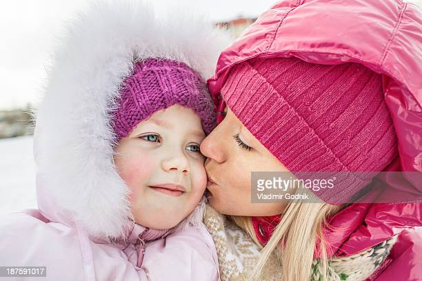 a mother kissing her daughter outdoors in winter - nah stock-fotos und bilder