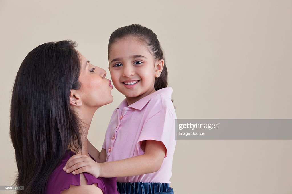 Mother kissing her daughter : Stock Photo