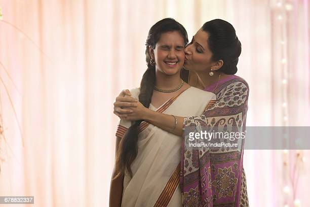 mother kissing her daughter - indian girl kissing stock photos and pictures