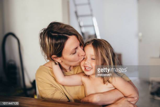 mother kissing her little daughter at new home - peuter stockfoto's en -beelden
