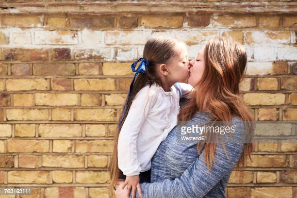 Mother kissing her little daughter in front of brick wall