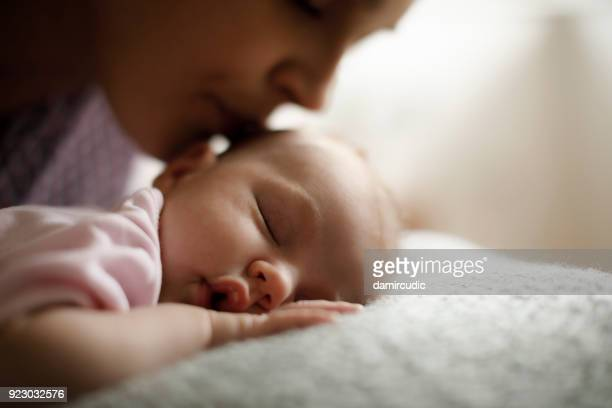 mother kissing her sleeping baby - girl chest stock photos and pictures