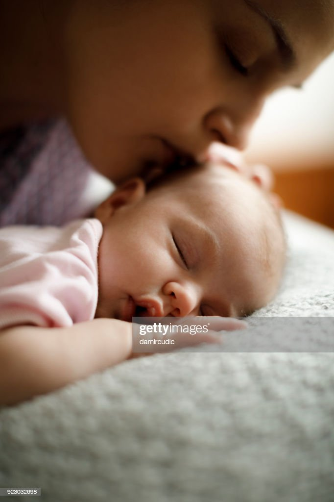 Mother kissing her sleeping baby : Stock Photo