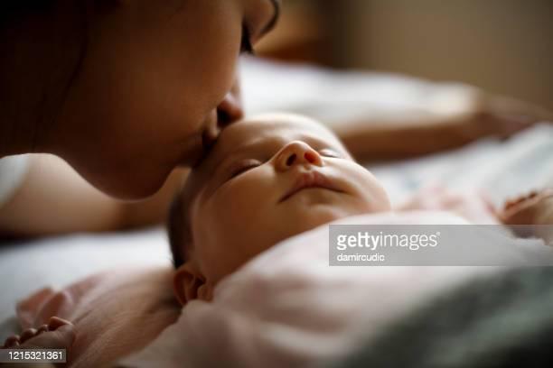 madre besando a su bebé recién nacido dormido - besar fotografías e imágenes de stock