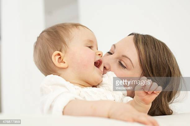 Mother kissing her smiling baby girl