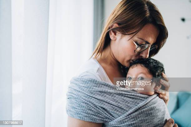 mother kissing her son in sling. - shawl stock pictures, royalty-free photos & images