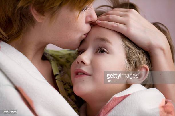 Mother kissing her son on the forehead