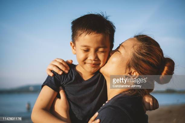 mother kissing her son's cheek - マレーシア ストックフォトと画像