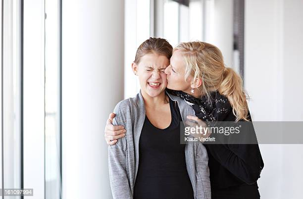 Mother kissing & hugging her daughter