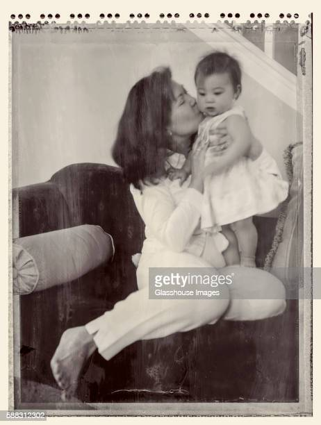 mother kissing infant daughter, polaroid - transfer image stock pictures, royalty-free photos & images