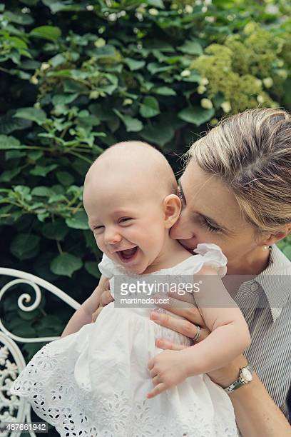 """mother kissing laughing baby girl on the neck, outdoors summer. - """"martine doucet"""" or martinedoucet stock pictures, royalty-free photos & images"""