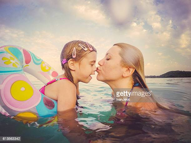 Mother kissing little daughter in sea