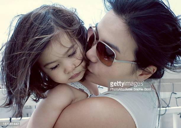 Mother kissing little girl's cheek