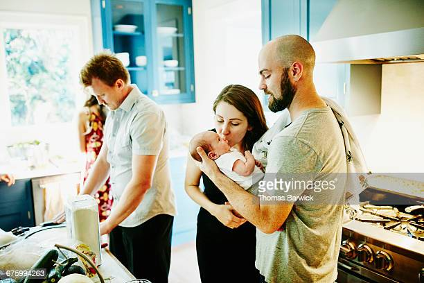 Mother kissing newborn baby while father holds him