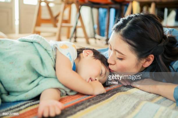 Mother kissing sleeping boys head