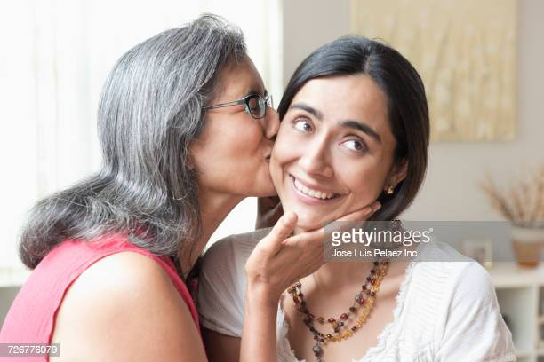 mother kissing smiling daughter on cheek - cheek stock pictures, royalty-free photos & images