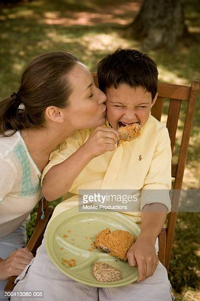 Mother kissing son (8-10), eating fry chicken