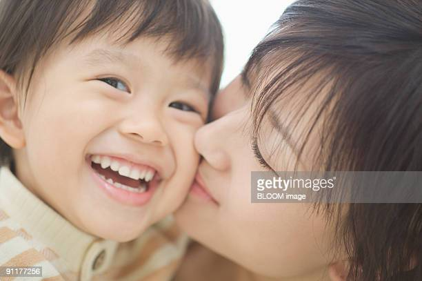 mother kissing son on cheek, smiling - 頬 ストックフォトと画像