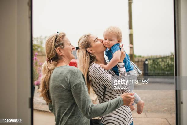 mother kissing son on the cheek - british granny stock photos and pictures
