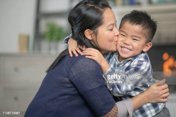 mother kissing son on the cheek - daily life in philippines stock pictures, royalty-free photos & images