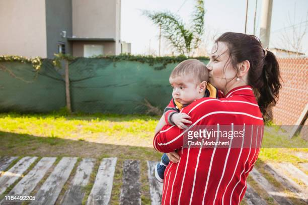 mother kissing son - santa fe province stock pictures, royalty-free photos & images