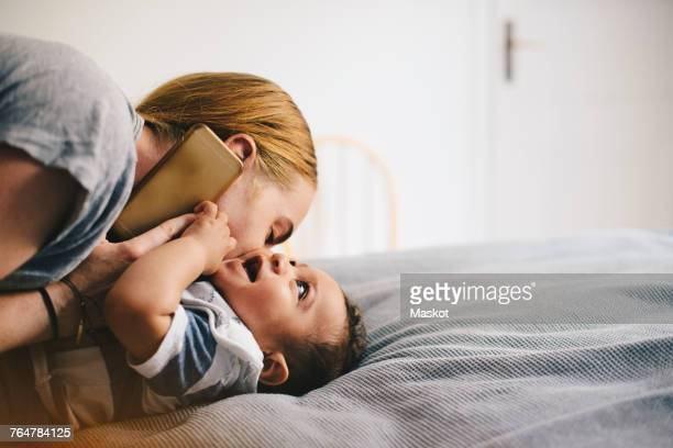 Mother kissing son while talking on mobile phone at bed
