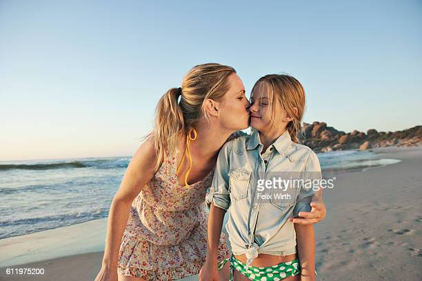Mother kissing with daughter (10-12) on beach