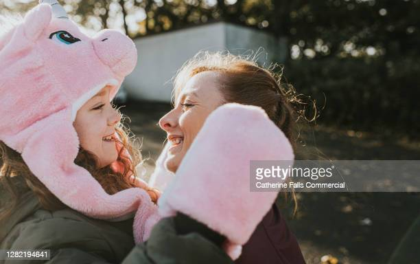 mother kneels in front of daughter and they smile at each other - headwear stock pictures, royalty-free photos & images