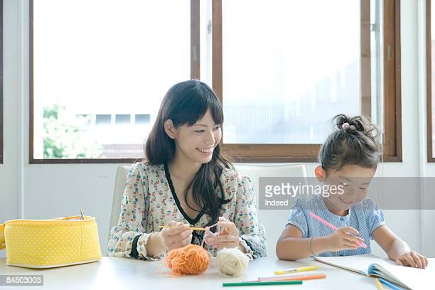 Mother knitting, girl doing homework at table