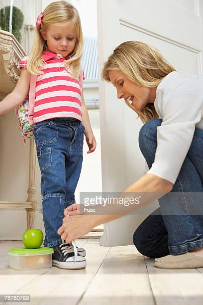 Mother Lacing Daughters Shoes