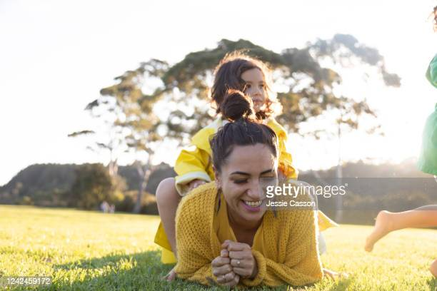 mother laughing as one daughter is sitting on top of her and the other is running - wellness stock pictures, royalty-free photos & images