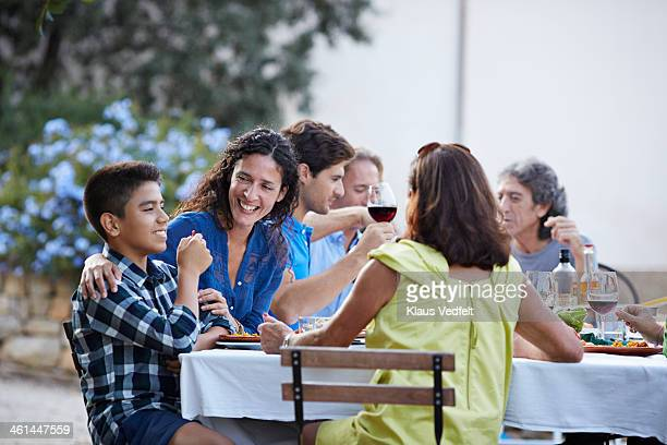 Mother laughing & looking at son at dinner