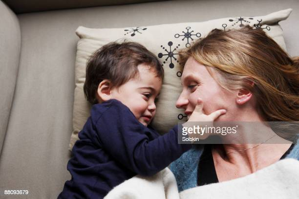 mother laying on sofa with son