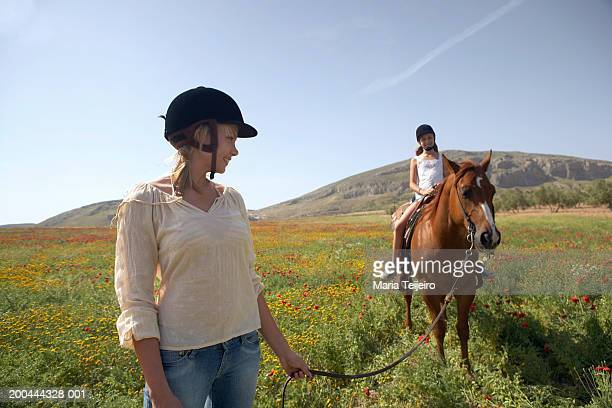 Mother leading daughter (10-12) riding horse in field, smiling