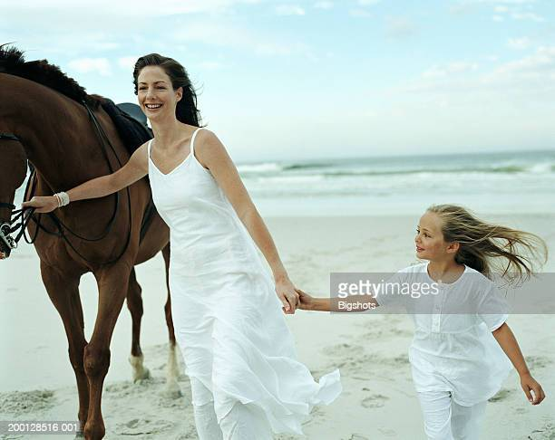 Mother leading horse on beach, holding hands with daughter (5-7)