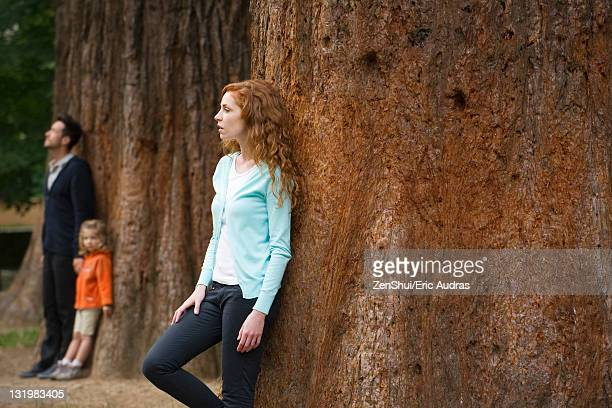 Mother leaning against tree trunk, husband and daughter separate in background