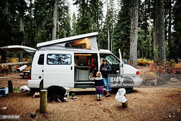 mother leaning on camper van looking at smartphone - camper stockfoto's en -beelden