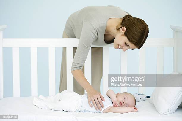 Mother leaning over side of crib to check sleeping infant
