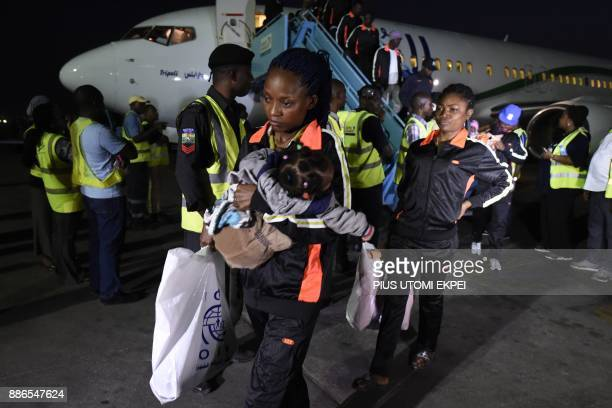 A mother leaves a chartered aircraft that brought home 150 migrants from Libya at the Murtala Mohammed International Airport in Lagos on December 5...