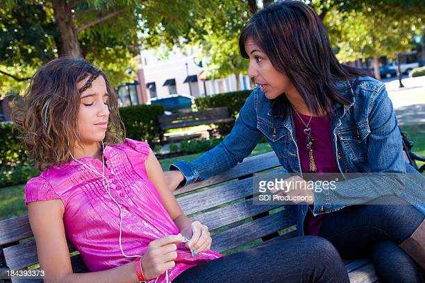 Mother lecturing her teenage daughter at a park