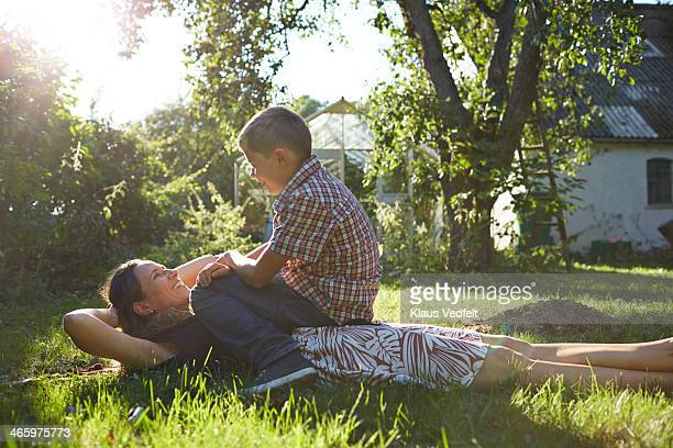 Mother lies on lawn laughing, son sitting on top
