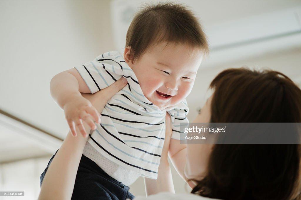 母 リフティング笑顔の赤ちゃん。 : ストックフォト