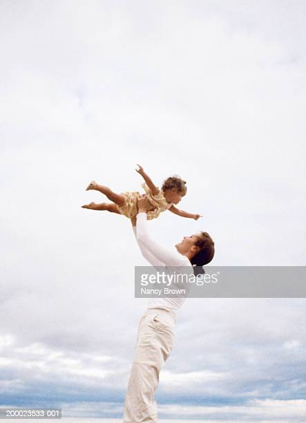 Mother lifting baby girl (12-15 months) overhead at beach, low angle
