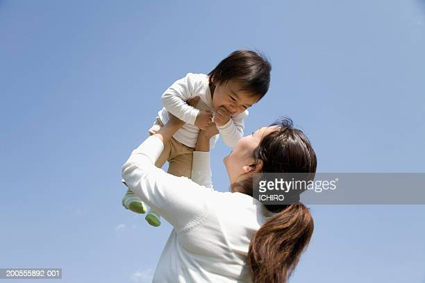 Mother lifting baby (12-15 months) outdoors